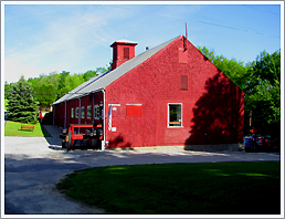 Photograph of a large red barn with trees in the background next to a gravel parking lot and road.